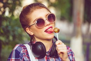 Hipster girl licking lollipop