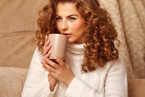Pretty girl drinking a hot drink.