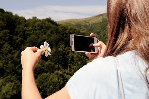 Girl taking a photo of a flower