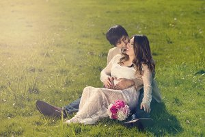 Expecting couple resting in field