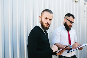 Two bearded businessman looking at something