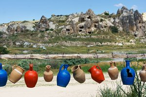 Colorful clay jugs hanging in a line with a mountain view, Cappadocia, Turkey.