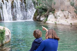 Mother with kid looking at waterfall