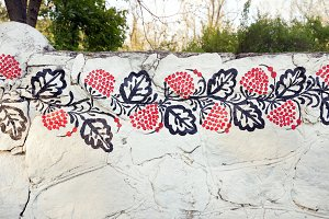 Petrykivka traditional ukrainian painting on the white stone fence