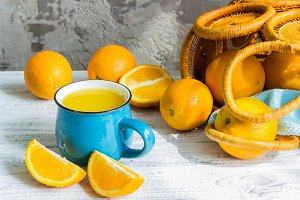 Orange juice glass and fresh oranges