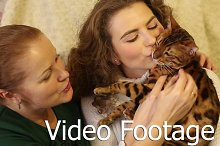 Mother and daughter playing with cat