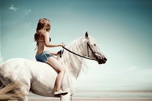 girl riding a horse near the sea