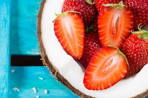 Coconut and strawberries on blue