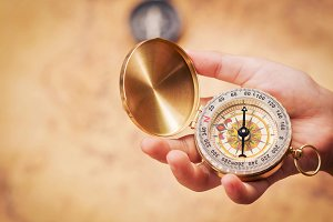 Child hand holding a compass