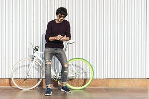 Young man with mobile and bicycle.