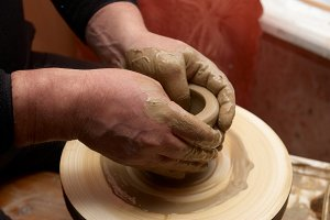 Female hands forming clay pot
