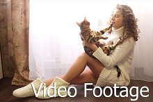 Girl hugs bengal cat on the floor.
