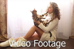 Girl hugs bengal cat on the floor.
