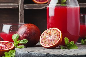 Juice with red oranges, square image