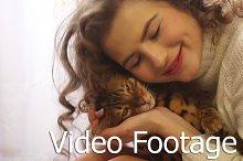 Girl kissing a Bengal cat.