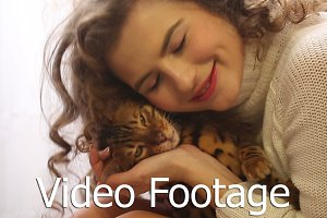 Girl kissing a Bengal cat.