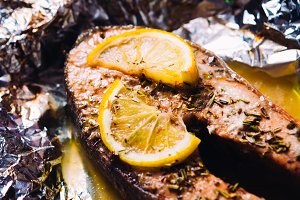 fish steak baked with lemon and herbs in foil