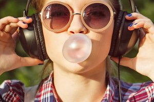 Girl listening to music. Chews cud