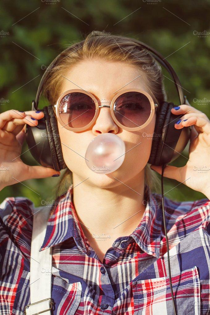 Girl listening to music. Chews cud - People
