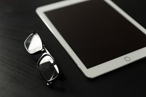 White iPad + glasses on black desk