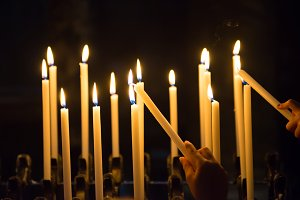 Hand lights candels in the church