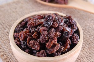 dry raisins in wooden bowl