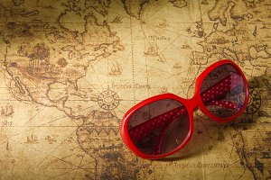 Red sun glasses on old map