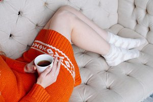 Woman legs with cup of tea