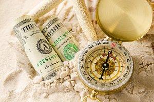 compass and sea shells on sand