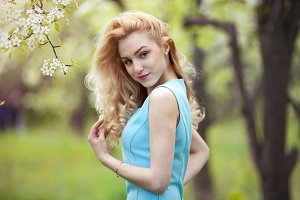 Beautiful woman spring portrait, smiling girl with flowers outdoor,  carefree young woman on nature