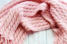 pink  woolen blanket on wooden table