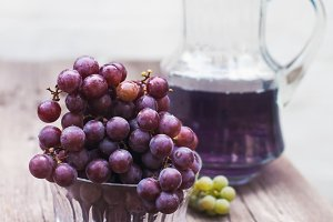 Fresh green  blue grapes and carafe of grape juice  on wooden table