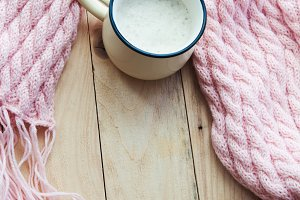 top view image of a pink cosy knitted scarf with a Cup of coffee on wooden table