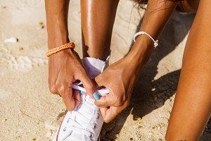 Beautiful black girl tying laces.