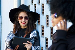 girls with tablet on the street