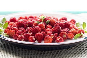 Wild strawberries on green table