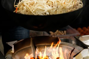 street food. fried noodles in a wok with chicken and prawns