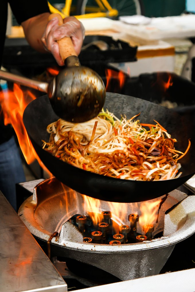 street food. fried noodles in a wok with chicken and prawns - Food & Drink
