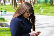 Beautiful woman in glasses uses cell smartphone outdoors in the park  - detail . Young attractive happy girl relaxes in a city park and uses a mobile phone. She looks very happy and contented