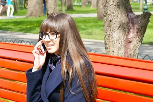 Young woman in glasses talking on the modile phone in a city park.