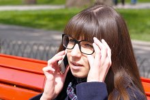 Young woman puts on glasses and talking on the modile phone in a city park. Girl sitting on a red bench outdoor in spring and speaking on smartphone. Close-up