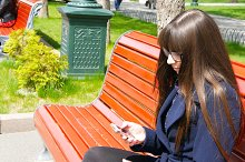 Young woman in glasses uses cell smartphone in a city park. Girl sitting on a red bench outdoor in spring and uses a mobile phone. Close-up