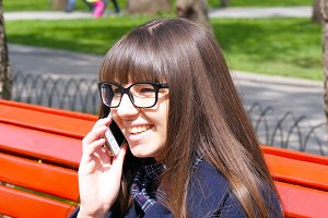 Young woman in glasses talking on the modile phone in a city park. Girl sitting on a red bench outdoor in spring and speaking on smartphone. Close-up