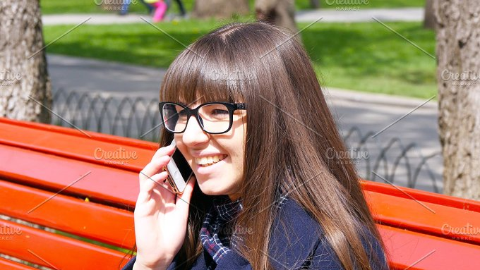 Young woman in glasses talking on the modile phone in a city park. Girl sitting on a red bench outdoor in spring and - People