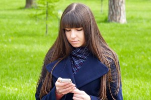 Beautiful woman uses cell smartphone outdoors in the park  - detail . Young attractive happy girl relaxes in a city park and uses a mobile phone. She looks very happy and contented