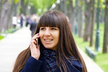 Attractive young woman in blue coat talking on the mobile phone in the alley in the park. Happy girl talking on smartphone, outdoors. Close-up