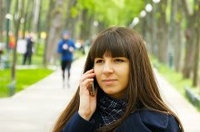 Attractive young woman in blue coat talking on the mobile phone in the alley in the park.