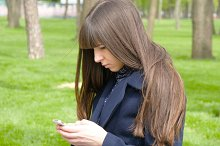 Beautiful woman waiting for meet in the park  - detail. She looking around and uses mibile smart phone.
