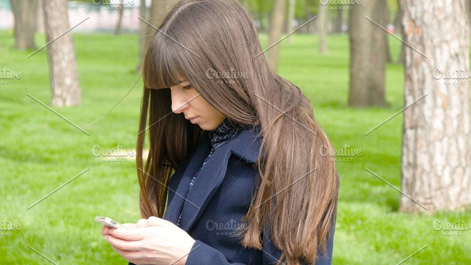 Beautiful woman waiting for meet in the park - detail. She looking around and uses mibile smart phone. - People