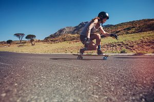 Young woman longboarding on a road